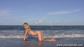 Extremely sexy blond-haired girlfriend posing half-naked on the shore