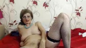 Glasses-wearing GILF in fishnets fingering her wrinkly pussy on webcam