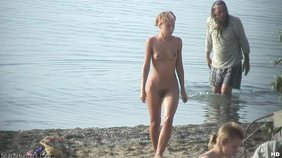 Blond-haired amateur washing her naked body in the water at a nudist beach