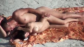 Tanned brunette with perky breasts about to get fucked sideways on a beach