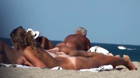 Tanned beauty with great-looking breasts sunbathing naked on a beach