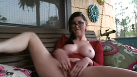 Glasses-wearing brunette minx fingering her juicy pussy on her porch
